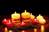 Beautiful candles and decor on wooden table on black background — Stock Photo