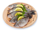 Fresh fishes with lemon, parsley and spice on wooden cutting board isolated on white — Stock Photo