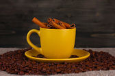 Composition of the yellow cup with coffee beans and cinnamon on wooden background — Stock Photo