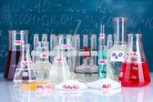 Tubes à essais avec divers acides et autres produits chimiques sur l'arrière-plan du tableau noir — Photo
