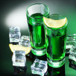 Two glasses of absinthe, lemon and ice on green background — Stock Photo #10430072