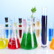 Different laboratory glassware with color liquid on blue background — Stock Photo