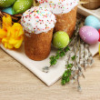 Beautiful Easter cakes, colorful eggs in basket and candles on wooden table - Stock Photo