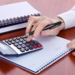 Woman hands with pencil, notebooks and calculator on wooden table — Stock Photo
