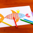Childrens drawing of golden fish and pencils on wooden background — Stock Photo