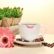 Cup of coffee with lipstick mark and gerbera beans, cinnamon sticks on wooden table — Stock Photo #10430567