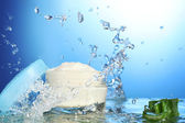 Opened jar of cream in water splashes on blue background — Stock Photo