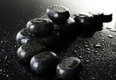 Spa stones with drops on grey background — Stock Photo
