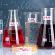 Test-tubes with various acids and other chemicals on the background of the blackboard - Stock Photo