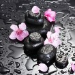 Spa stones with drops and pink sakura flowers on grey background - Lizenzfreies Foto