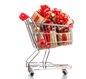 Beautiful golden gifts with red ribbon and Christmas balls in shopping cart isolated on white — Stok fotoğraf
