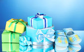Beautiful gifts and babys bootees on blue background — Stock Photo