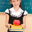 Beautiful little girl in school uniform with books and apple in class room — Stock Photo