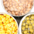 Open tin cans of corn, beans and peas close-up isolated on white — Stock Photo