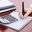 Women hands with pencil, notebooks and Calculator on wooden table — Stock Photo