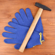 Hammer and gloves on wooden background - Stock Photo