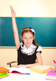 Beautiful little schoolgirl in classroom — Stock Photo