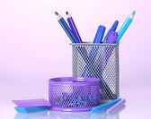 Barvy držáky pro kancelářské potřeby s nimi na světlé barevné pozadí — Stock fotografie
