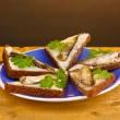 Tasty sandwiches with sprats on plate on wooden table on brown background - Stock Photo