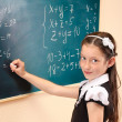 Beautiful little girl writing on classroom board — Stock Photo #10497019