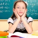Beautiful little schoolgirl in classroom — Stock Photo