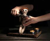 Voodoo docka flicka genomborrad av kniv på ett träbord i levande ljus — Stockfoto