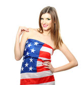 Beautiful young woman wrapped in American flag isolated on white — Stock Photo