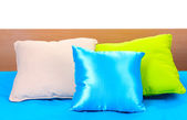 Bright pillows on bed on white background — Stock Photo