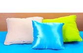 Яркие подушки на кровати на белом фоне — Стоковое фото