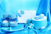 Beautiful gifts, babys bootees, blank postcard and dummy on blue silk — Stock Photo