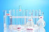 Tubos de ensayo con varios ácidos y productos químicos sobre fondo azul — Foto de Stock