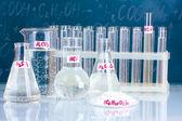 Probówki z różnych kwasów i innych środków chemicznych na tle tablicy — Zdjęcie stockowe
