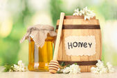 Sweet honey in barrel and jar with acacia flowers on wooden table on green background — Stock fotografie