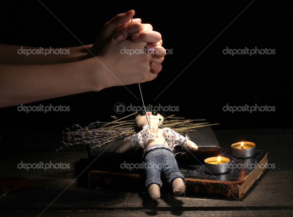 Voodoo doll boy pierced by a needle on a wooden table in the candlelight — Stock Photo #10496283