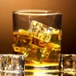 Glass of whiskey and ice on brown background - Stock Photo
