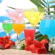 Exotic cocktails and flowers on table on blue sky background — Stock Photo