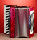 Retro accordion on wooden table on red background — Stock Photo