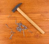 Chiodi martello e metallo su fondo in legno — Foto Stock
