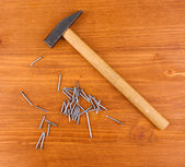 Clavos martillo y metal sobre fondo de madera — Foto de Stock