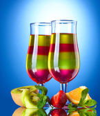 Fruit jelly in glasses and fruits on blue background — Stock Photo