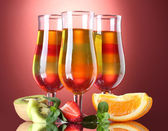 Fruit jelly in glasses and fruits on red background — Stock Photo