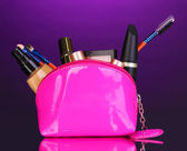 Que el bolso con cosméticos y cepillos sobre fondo violeta — Foto de Stock