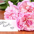 Stock Photo: Pink peony with card on wooden background
