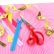 Scissors, zips and measuring tape on fabric isolated on white - Stock Photo