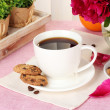 Cup of coffee, cookies, orange and flowers on table in cafe — Stock Photo