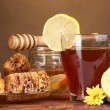 图库照片: Honey, lemon, honeycomb and a cup of tea on wooden table on brown background