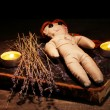 Foto Stock: Voodoo doll girl on a wooden table in the candlelight