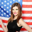 Beautiful young woman with the American flag on the background — Stok Fotoğraf #10586050