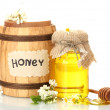 Sweet honey in barrel and jar with acacia flowers isolated on white — Stock Photo #10586117