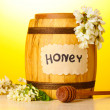 Sweet honey in barrel with acacia flowers on wooden table on yellow background — Stock Photo